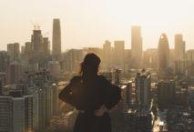 Frau blickt auf Metropole; Foto: iStock.com/Wenjie Dong