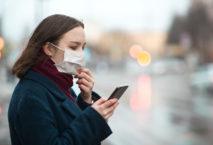 Frau mit Mundschutz und Smartphone; Foto: iStock.com/ArtMarie