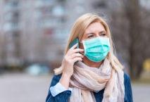 Frau mit Smartphone und Mundschutz; Foto: iStock.com/ti-ja