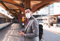 Berufspendler mit Mundschutz auf Bahnsteig; Foto: iStock.com/luza studios