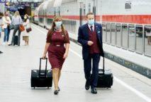 Zwei Zugbegleiter der Deutschen Bahn mit Mundschutz und Rollkoffer auf Bahnsteig; Foto: DB / Volker Emersleben