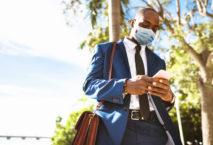 Mann im Anzug mit Mundschutz, Smartphone und Arbeitstasche; Foto: iStock.com/franckreporter